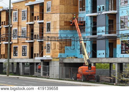 NORWALK, CT, USA - APRIL 29, 2021:  New construction building on Route 1 with person working on lift outside