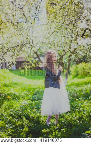 Cute Girl In Black Jacket With Long Hair Standing In Spring Cherry Garden. Portrait Of Happy Child A
