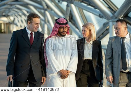 A group of intercultural people in formalwear standing in a building