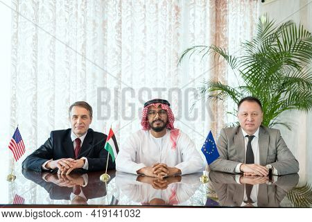 A group of confident intercultural businessmen in formalwear sitting in row by table