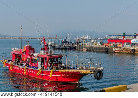 Daecheon, South Korea; April 25, 2021: Red Fishing Boat About To Dock At Seaport Under Overcast Sky.