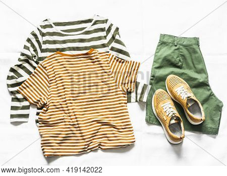 Women's Cotton Bermuda Shorts, Two T-shirts, Yellow Leather Sneakers On A Light Background, Top View
