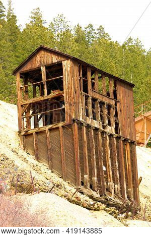 Abandoned Dilapidated Historical Wooden Mine On An Eroded Mountain Slope Surrounded By An Alpine Pin