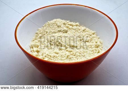 Grated Italian Parmigiano Reggiano Cheese In A Red Bowl Isolated On White Background