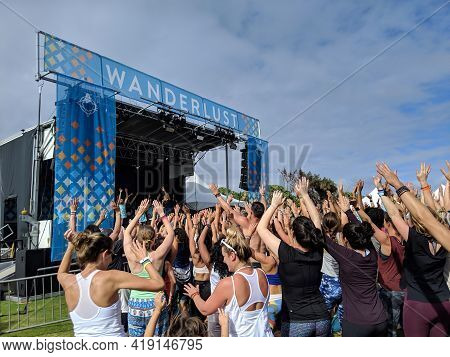 North Shore, Oahu - March 3, 2019: People Wave Hands In The Arm By Stage At Wanderlust Mc Yogi Yoga