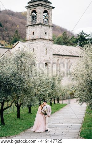 Newlyweds Walk In An Olive Grove Against The Background Of An Old Tower With Bells On Lake Como
