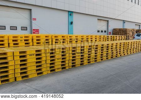 Daecheon, South Korea; April 25, 2021: Plastic Yellow Pallets Stacked Neatly Behind Warehouse.