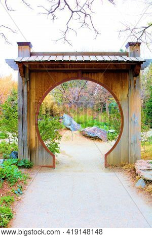 April 26, 2021 In Denver, Co:  Pedestrian Pathway Underneath A Decorative Zen Sculpture Surrounded B