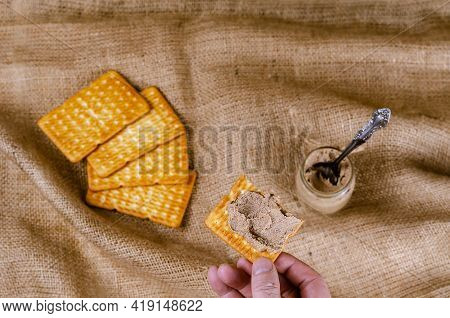 High Angle View Of A Hand Holding A Cracker With Liver Pate. Man Holding Half Of A Snack With Pate S