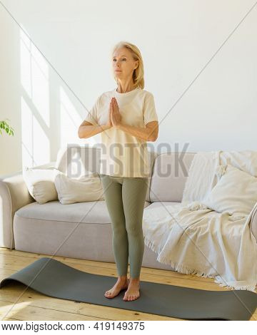 Balance In Life. Calm Peaceful 60s Senior Woman Practicing Yoga And Meditating While Exercising On M