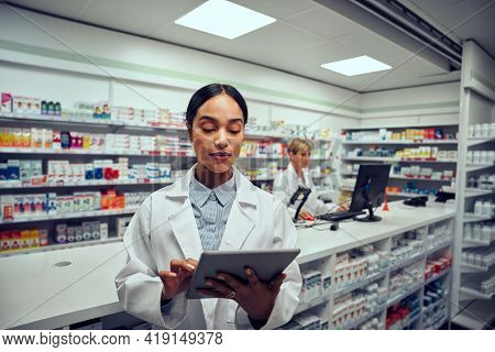Portrait Of Young Female Working In Pharmacy Wearing Labcoat Standing While Using Digital Tablet To