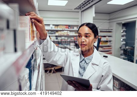 Woman Wearing Labcoat Holding Digital Tablet Searching For Medicine In Shelves Of Pharmacy