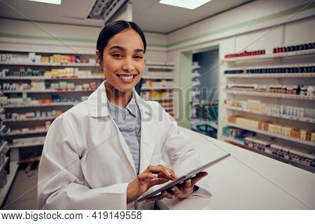 Portrait Of Smiling Young Female Pharmacist Wearing Labcoat Standing Behind Counter Using Digital Ta