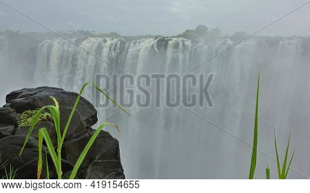 The Powerful Streams Of Victoria Falls Plunge Into The Abyss. A Thick Mist Of Water Spray Hides Ever