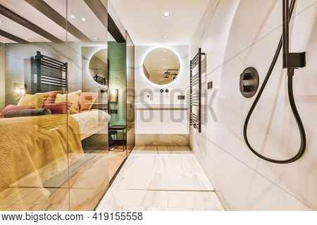 Interior Of Narrow Washroom With Glass Wall Located Near Bedroom In Modern Apartment