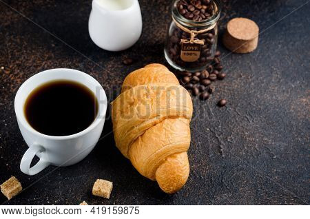 Fresh Croissant With A Mug Of I Black Coffee And Coffee Beans On Dark Concrete Background. The Conce