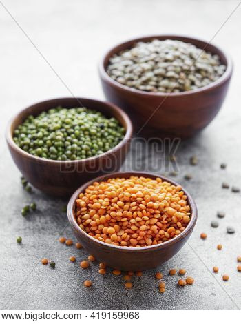Bowls With Different Types Of Legumes On A Gray Concrete Background
