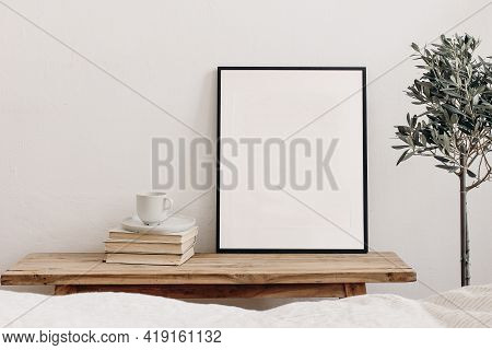 Vertical Black Picture Frame Mockup On Vintage Bench, Table. Cup Of Coffee On Pile Of Books. Potted