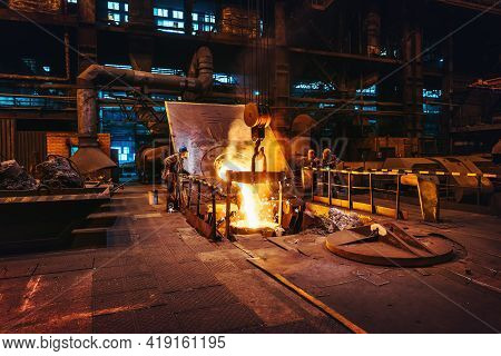 Foundry Workshop Interior, Molten Iron Pouring From Blast Furnace Into Ladle Container And Workers F