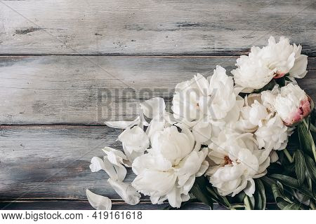 Feminine Wedding Table Composition With White Peonies Flowers On Old Shabby Wooden Background. Empty