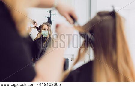 Hair stylist and customer during coronavirus pandemic wearing mask