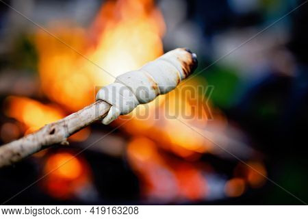Stick Bread Twisted On Skewer Or Stick, Roasted On Flame Of Fire. Popular Party And Camp Barbecue Fo