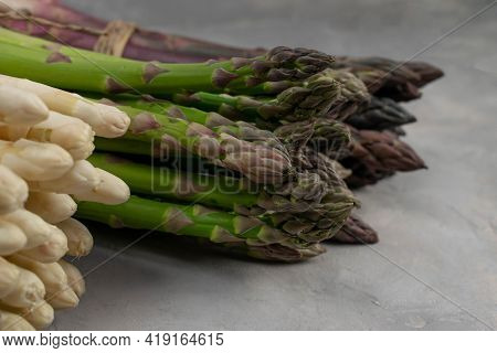 Three Bunches Of Different Fresh Asparagus Isolated On Grey. Purple White And Green Asparagus. Close