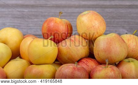 heap of bright ripe apples on wooden background