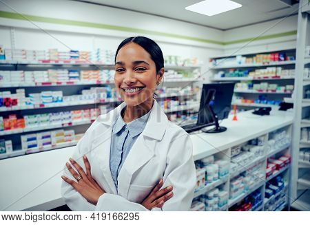 Cheerful Young Woman In Labcoat Standing With Folded Hands In Chemist
