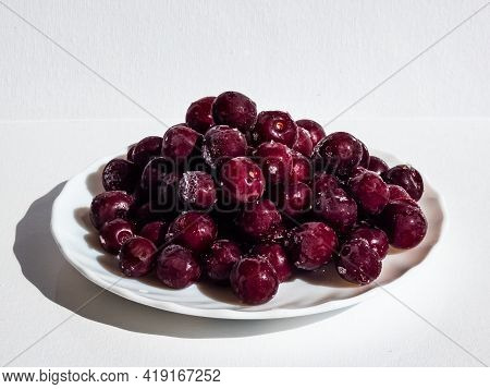Frozen Sweet, Ripe Cherry Berries Covered With Hoarfrost On White Plate With White Background In Bri