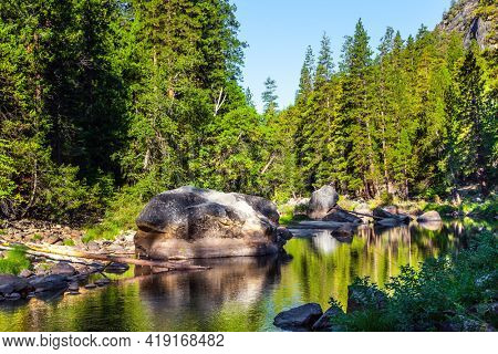 Charming little lake in the Yosemite Valley. The shady forest is reflected in the water. Yosemite Park is located on the slopes of the Sierra Nevada