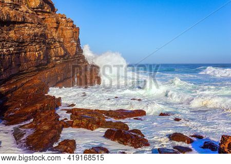 Powerful ocean surf. Cape of Good Hope at the southern tip of the Cape Peninsula. White foam of the ocean surf. South Africa. Bright sunny summer february day