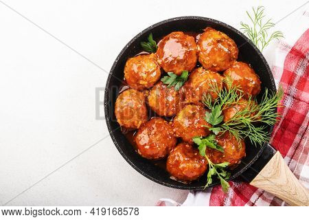Meatballs With Spicy Tomato Sauce In Frying Pan On White Kitchen Table. Top View