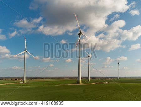 Aerial view of large wind turbines with blades in field against blue sky and white clouds. Alternative energy. Wind farm generating green energy.