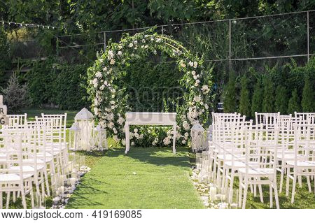 Wedding Ceremony. Very Beautiful And Stylish Roundwedding Arch, Decorated With Various Fresh Flowers
