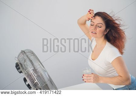 A Red-haired Caucasian Woman Chills By The Electric Fan And Drinks A Cold Drink. Climate Control In