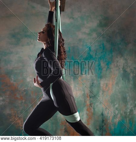 A Beautiful Young Woman In A Tight Black Tracksuit Does Yoga On A Suspension,