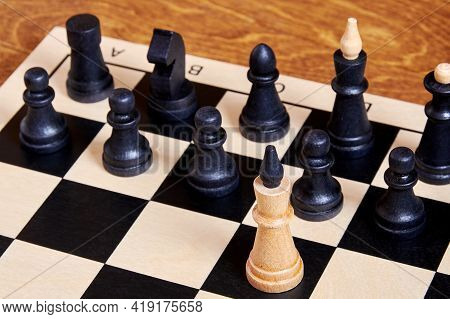 A Single Brave Leader Figure Attacks The Whole Black Chess Army. Chess Concepts And Symbols Represen