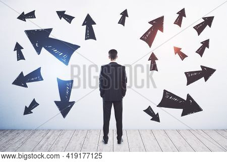 Businessman Standing Puzzled In Front Of A Wall With Multiple Black Arrows Pointed In Different Dire