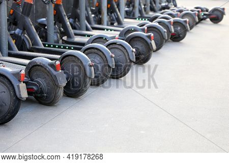 Electric Scooters In A Row On The Parking Lot. City Bike Rental System, Public E-scooters On The Str