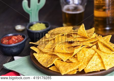 Nachos With Guacamole And Red Chilli Sauces On Wooden Table. Mexican Cuisine Background