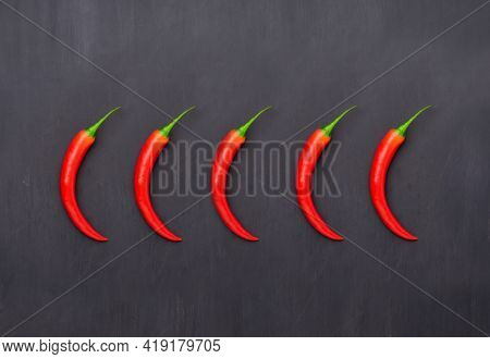 Selection of red Chilli peppers over grey background. Spicy food rating concept. Flat lay.
