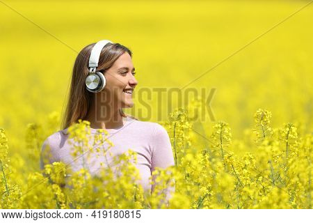 Happy Woman Listening To Music Wearing Headphones Contemplating Views In A Yellow Field In Spring Se