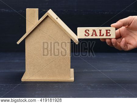 Wooden Model Of A House And A Hand Holds A Block With An Inscription  Sale On A Blue Background. Hou