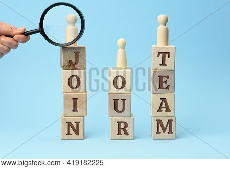 Wooden Figurines Of Men Stand On Cubes With The Inscription And A Hand With A Magnifying Glass On A