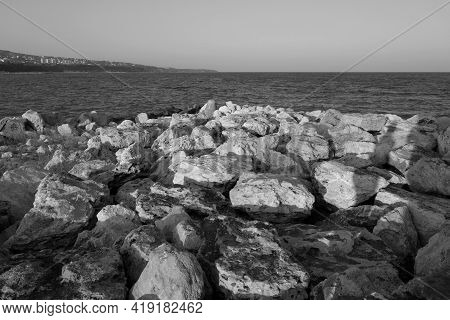 Stones Used As Breakwater At The Sea In Black And White. Sea View And Background.