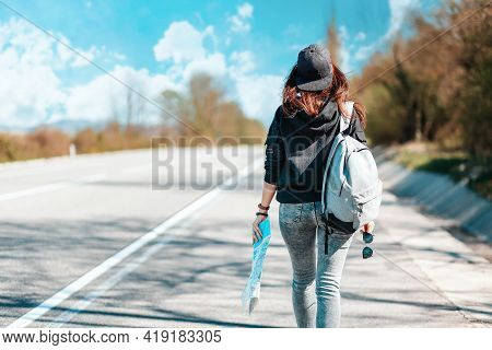 The Concept Of Hitchhiking Trips And Local Travel. Hipster Woman In A Cap, With Backpack Walking Dow