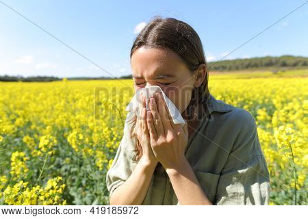 Woman Suffering Allergy Coughing In A Yellow Flowered Field In Spring Season