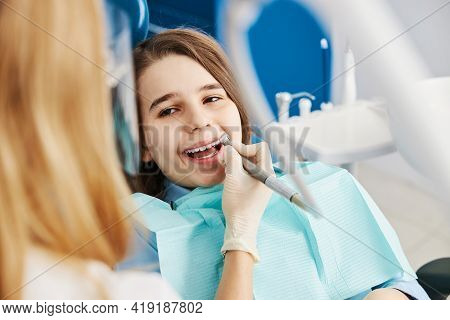 Stomatologist Drilling Boy Teeth With Dental Drill