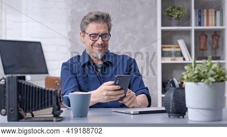 Bearded man working online with laptop computer and smart phone at home sitting at desk. Businessman in home office. Portrait of mature age, middle age, mid adult man in 50s.